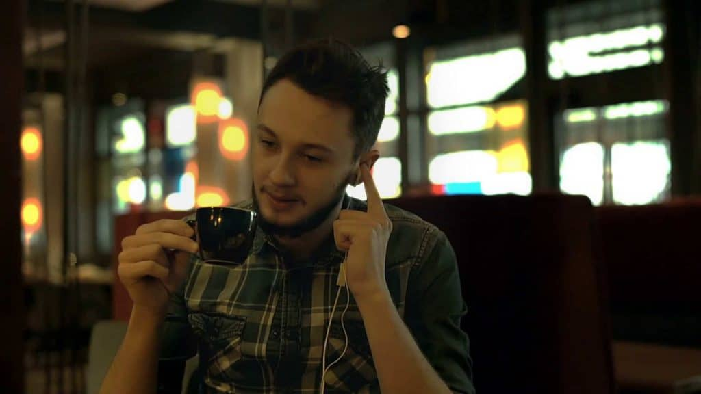person happy enjoying coffee with his earbuds