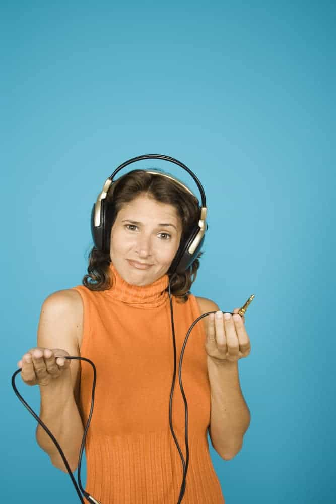 Portrait of woman holding end of unplugged headset