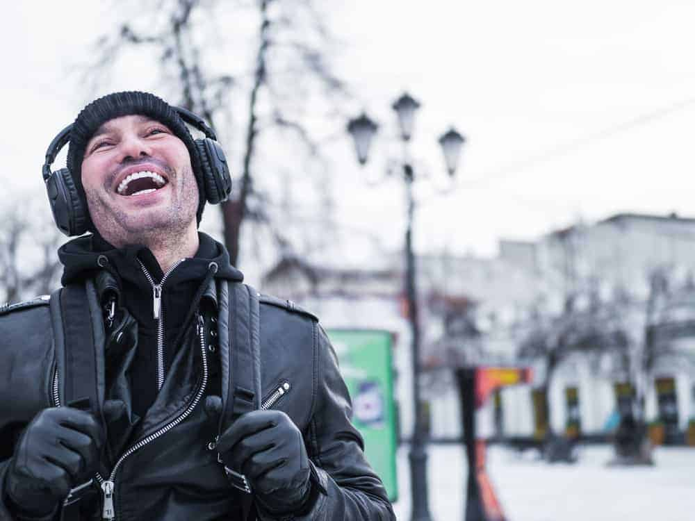 portrait of a young man laughing and listening to music at a street