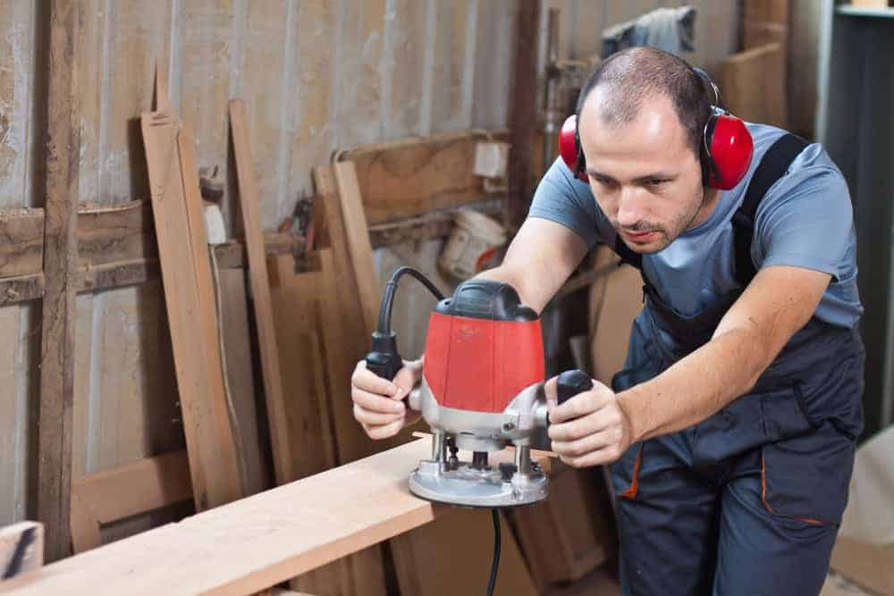 Worker with a router, horizontal with a noise active cancelling headphones