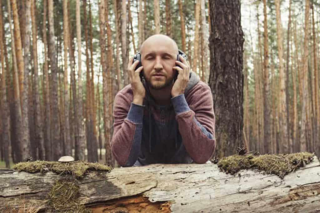 Man with headphones in a wild forest. Concept of a hiking trip t