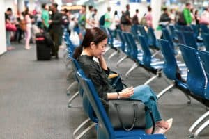 Woman using cell phone waiting for boarding at the airport terminal.