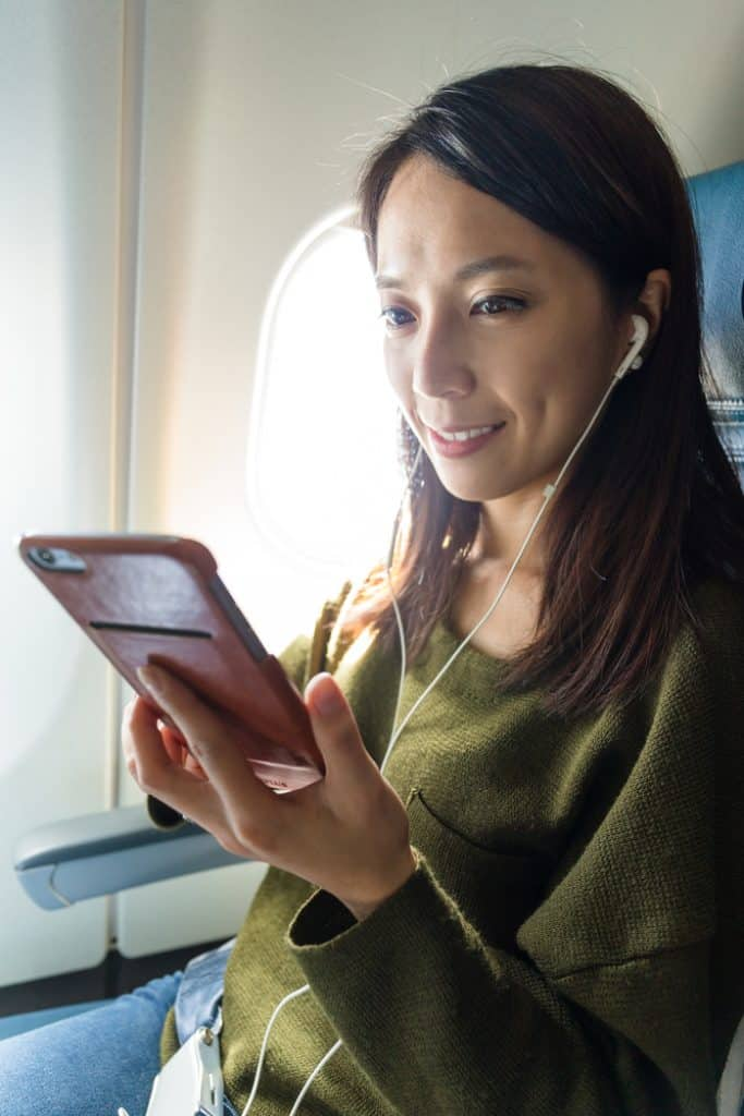 Woman passenger in airplane using cellphone with headphones