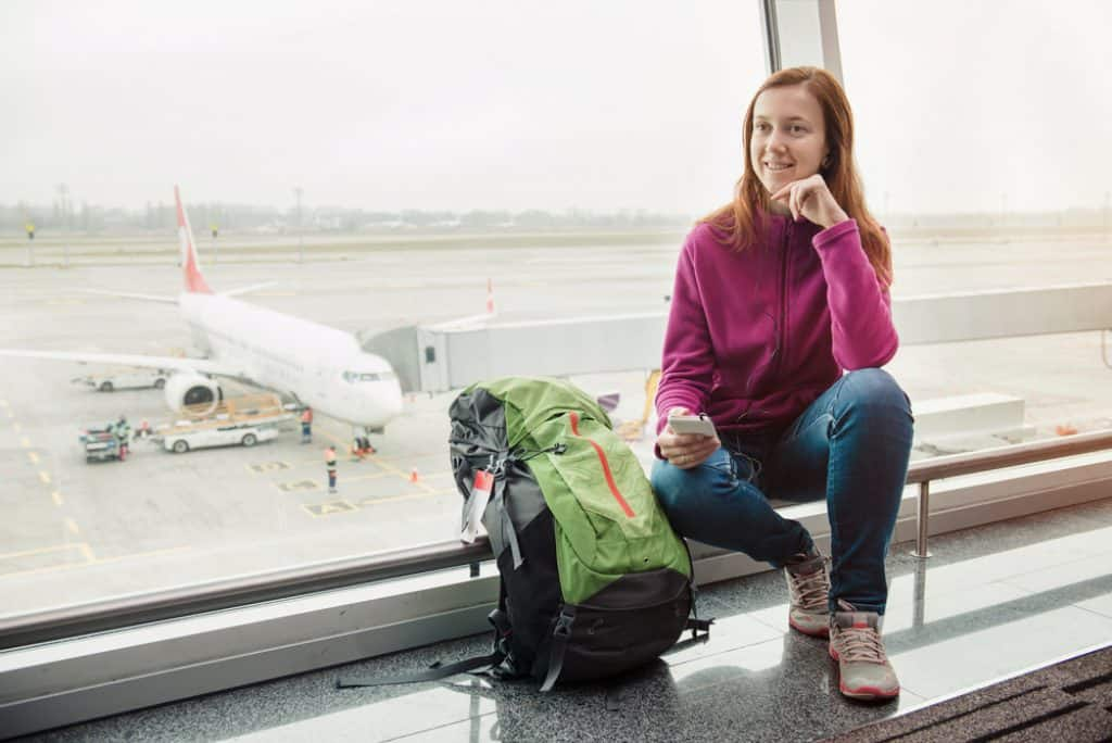 Woman waiting for flight and listening music in airport
