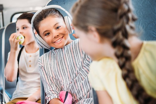 Beautiful Little schoolgirl listening music with headphones while riding on school bus with classmates