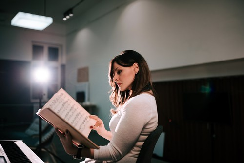 Image of female pianist sitting in front of a synthesizer holding sheet music