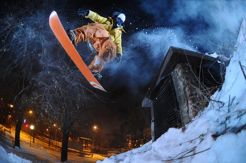 Jumping snowboarder is using this best headphones for snowboarding